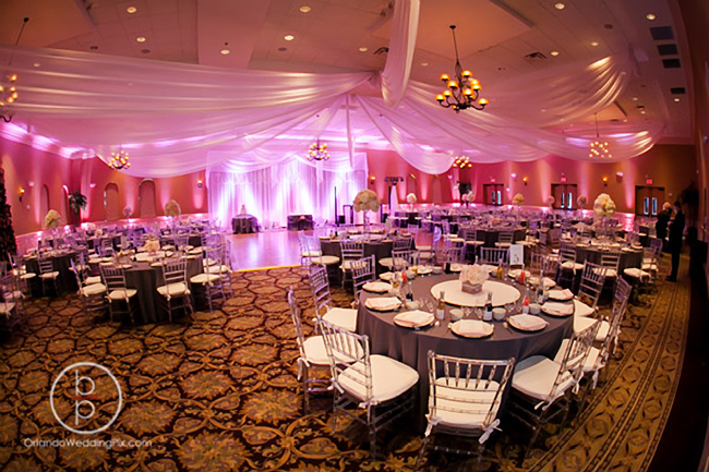 Custom event draping, and backdrop in white chiffon with decorative strings of crystal beads, chandeliers, and LED up-lights for a modern wedding reception at Holy Trinity Reception Center in Maitland, FL. Chiffon drapes and accessories by W Drapings. Photo by Brian Pepper of OrlandoWeddingPix.