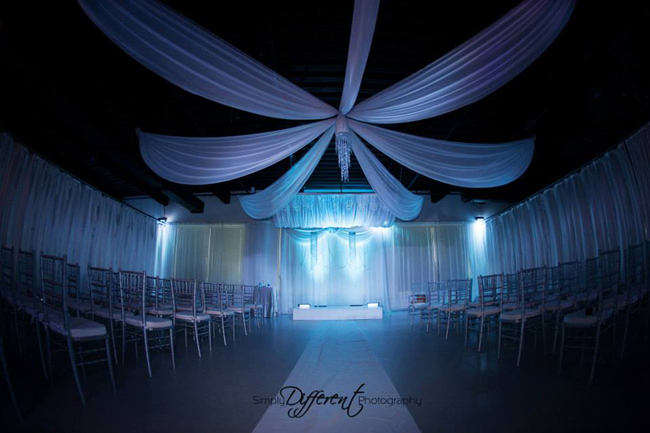 Custom ceiling draping, backdrop, and canopy in white chiffon with decorative strings of crystal beads, chandeliers and LED up-lights for a modern wedding reception at Heaven Event Center in Orlando, FL. Draping and accessories by W Drapings. Photo by Simply Different Photography.