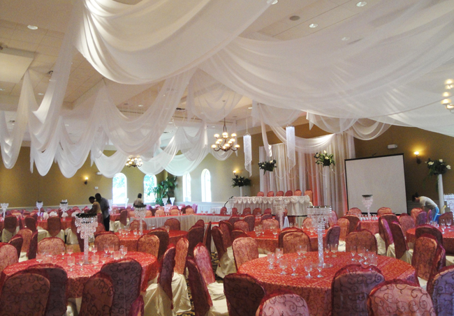 Classic wedding reception at Holy Trinity Reception Center in Maitland, FL with custom event draping and backdrop in white chiffon by W Drapings. Accessories include decorative crystal chandeliers. Photo and drapes by W Drapings.