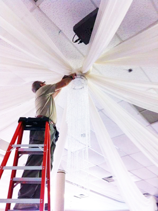Ernesto up in the ladder installing white chiffon ceiling treatments and a decorative crystal chandelier for a wedding in Orlando, FL. Photo by W Drapings.