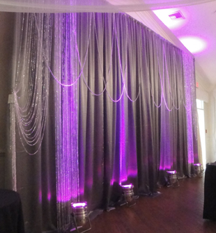 Custom backdrop in silver satin with decorative strings of crystal beads and purple LED up-lights. Photo, drapes and accessories by W Drapings.